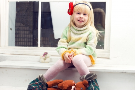 blonde little girl in knitted sweater sitting on the window Фото со стока