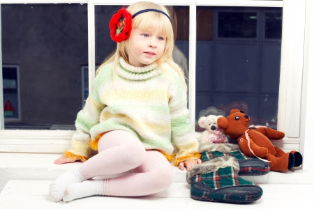 blonde little girl in knitted sweater sitting near the window of toys