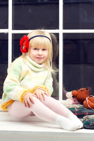 beautiful little girl blonde in a knit sweater sitting beside toys in the window and looks into the camera photo