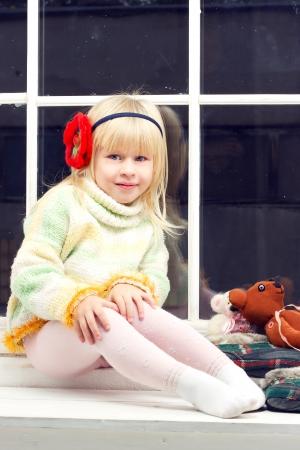 니트 스웨터 창에 장난감 옆에 앉아 카메라에 보이는 아름다운 어린 소녀 금발