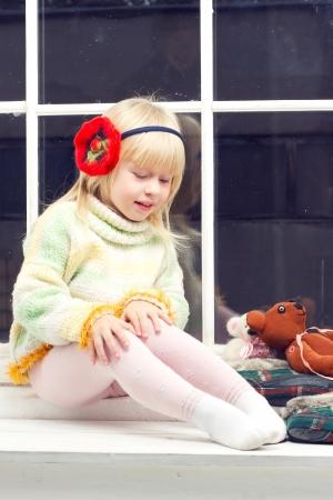 beautiful little girl blonde in a knit sweater sitting near the window of toys