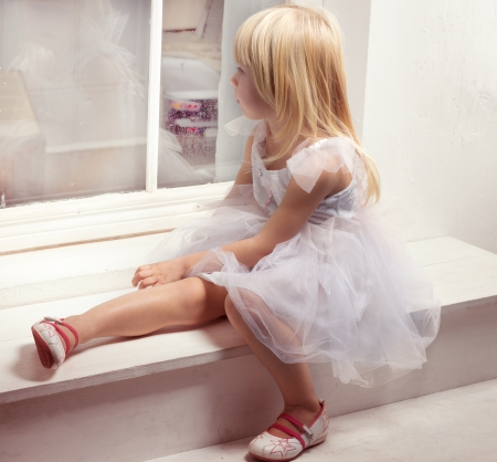 sill: Girl 3 years old in a beautiful white dress near the winter window Stock Photo