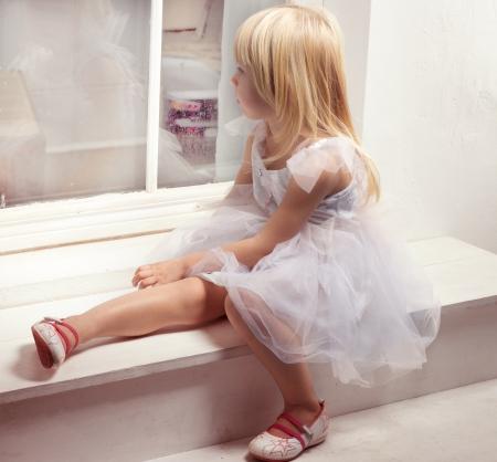 pretty little girl: Girl 3 years old in a beautiful white dress near the winter window Stock Photo