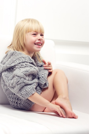Girl 3 years old in a gray knit sweater sitting on a sofa