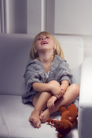 Little girl with bear on white sofa photo