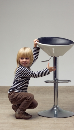 Blonde girl 3 years sat near a high chair and doing something Stock Photo