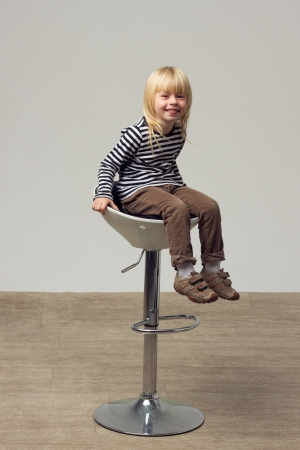 Blonde girl 3 years old in jeans sits on a high chair photo