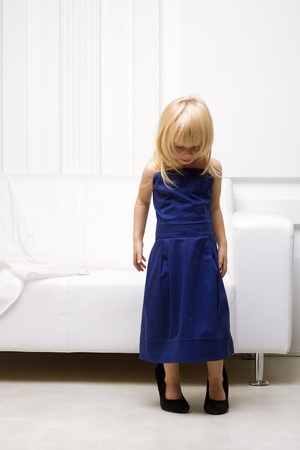 Little girl 3 years old standing near the white sofa in her mother photo