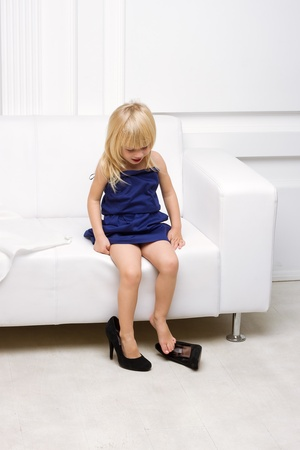Little girl 3 years old sitting on a white sofa in her mother Stock Photo