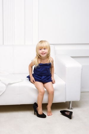 Little girl 3 years old sitting on a white sofa in her mother photo