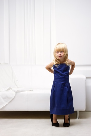 Little girl 3 years old standing near the white sofa in her mother Stock Photo
