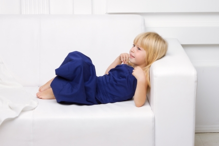3 years old girl is in a blue dress on a white sofa photo
