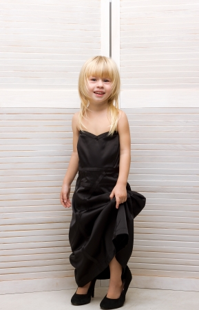 Girl 3 years old in my mothers black dress and high heels photo
