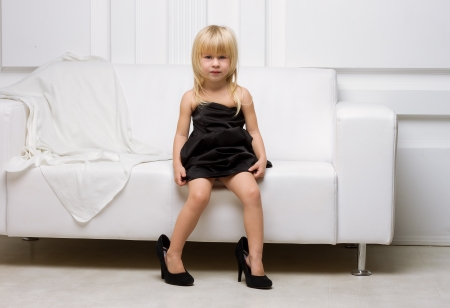 Girl 3 years old in her mother's high heels sitting on a white sofa photo