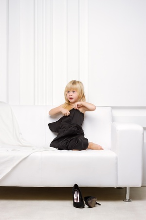3 years old girl lying on a white sofa in my mothers dress, standing next high heels Stock Photo