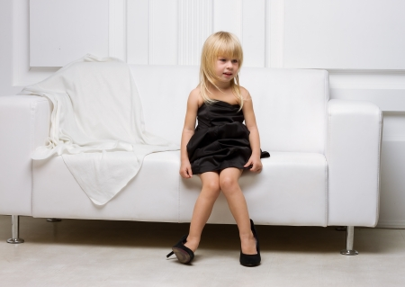 Girl 3 years old in her mothers high heels sitting on a white sofa Stock Photo
