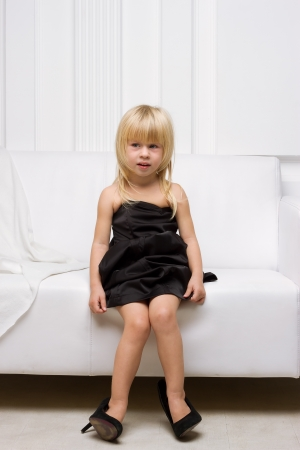 Girl 3 years old in her mothers high heels sitting on a white sofa photo