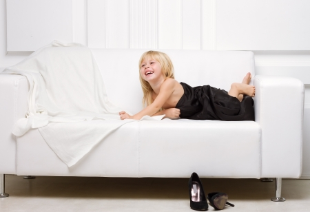 3 years old girl lying on a white sofa in my mothers dress, standing next high heels photo