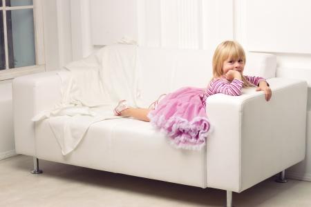 Little cute girl posing happily on sofa