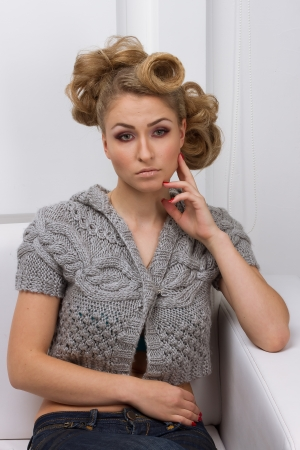 young, beautiful slim blonde girl in a gray jacket lying on a white sofa in a white studio photo