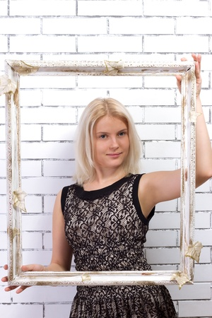 Beautiful blonde in a white dress with a frame in his hands Stock Photo - 17662403