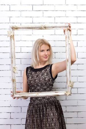 Beautiful blonde in a white dress with a frame in his hands Stock Photo - 17662406