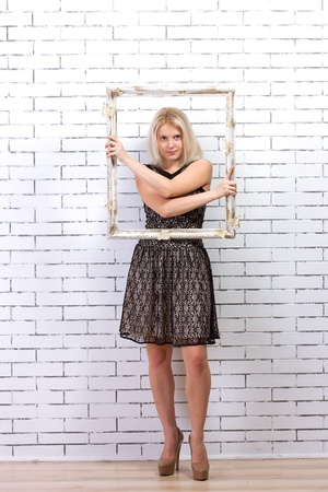 confiding: Beautiful blonde in a white dress with a frame in his hands