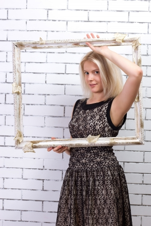 Beautiful blonde in a white dress with a frame in his hands Stock Photo - 17662402