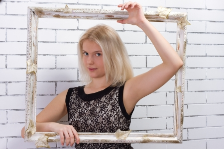 Beautiful blonde in a white dress with a frame in his hands Stock Photo - 17662401