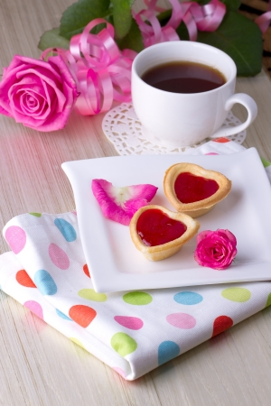 Holiday Tartlets with jam near the cup of tea on the background of roses photo
