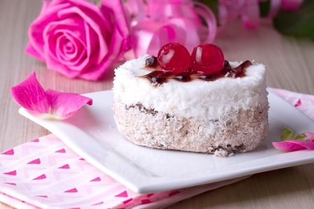 gumpaste: Celebratory cake with cherries on a background of pink roses Stock Photo