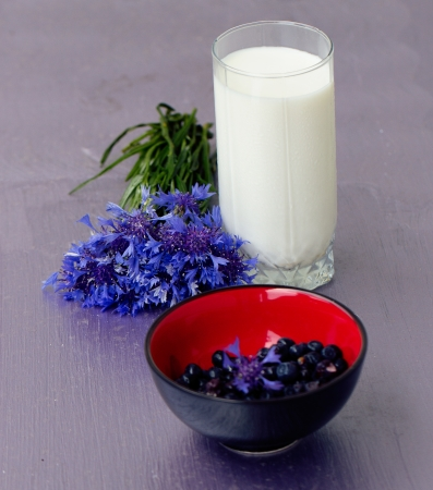 glass of milk and a bouquet of cornflowers on a purple table Stock Photo - 17575629