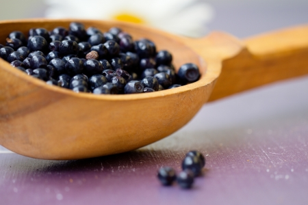 Fresh juicy blueberry fruits on a wooden spoon Stock Photo