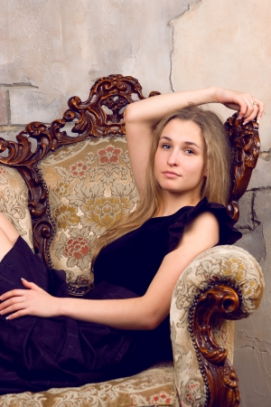 Beautiful sexual girl blonde pose in the chair on gray background Stock Photo