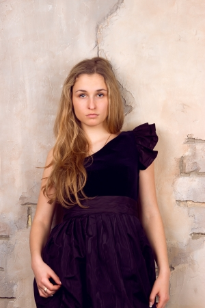 Beautiful blonde with her hair in a black dress near the wall photo