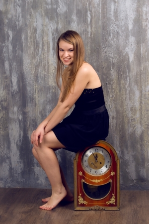 Beautiful smiling woman holding big clock