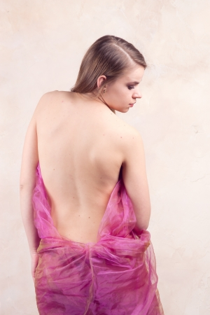 girl with a bare back on a beige background. Stock Photo