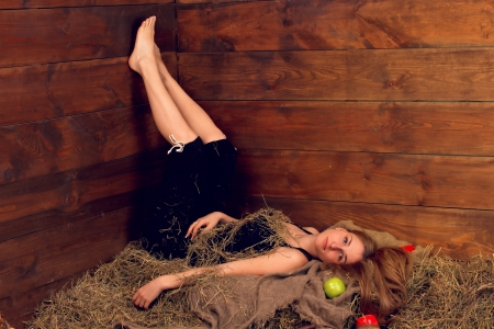 beautiful smiling woman with many apple in basket on haystack at farm
