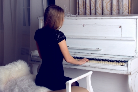 girl with blond long  hair in  dress playing white piano photo