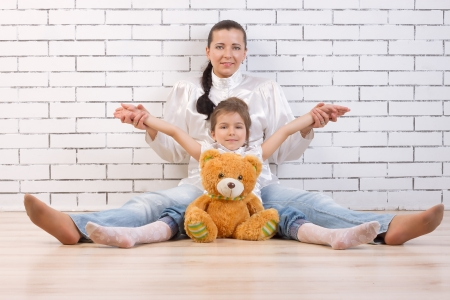 Mother, daughter and toy sitting against the wall photo
