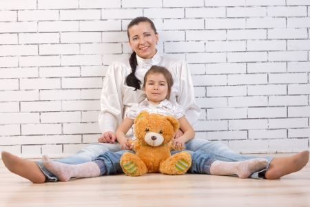 Mother, daughter  sitting near a white wall photo
