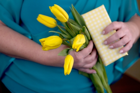 Yellow tulips in hands of the  female photo