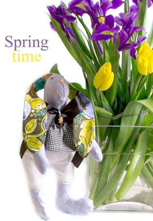 Homemade toy - rabbit near a bouquet of spring flowers photo