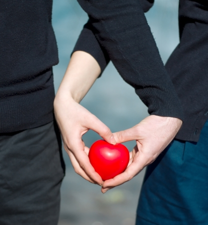 Man and woman are holding a red heart