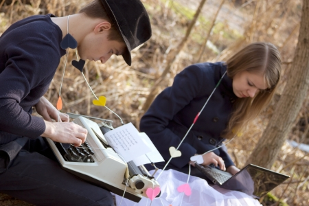 young man and woman typing on a typewriter in the park photo