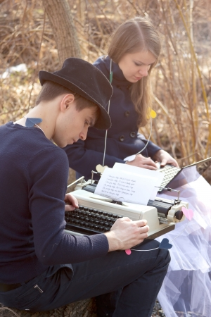 Young man typing on a typewriter in the park photo