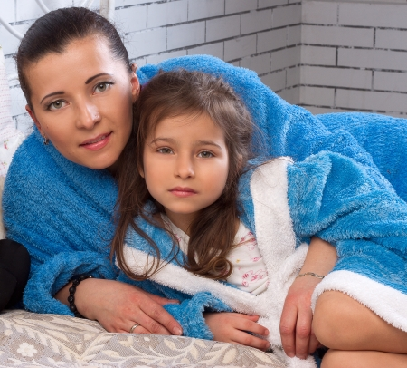 Mom and daughter in blue terry robes on the bed photo