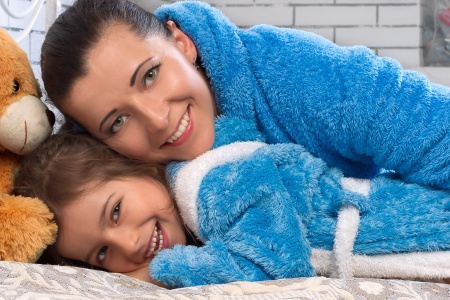 Happy mother and daughter in blue terry robes on the bed