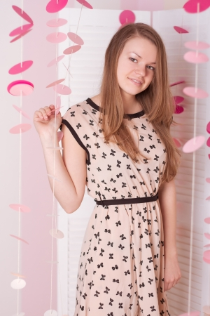 girl in the romantic interior in a dress and pink photo