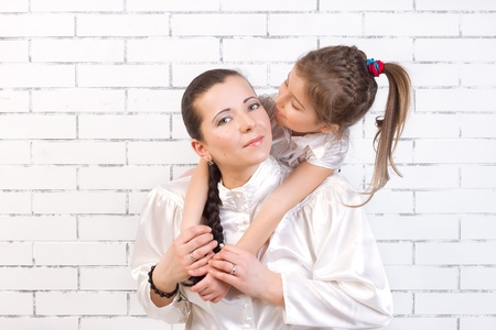 timidity: 5 year old daughter in a white dress kissing his mother Stock Photo